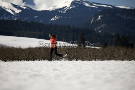 young woman runs through snow with