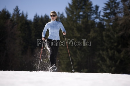young woman runs through snow with