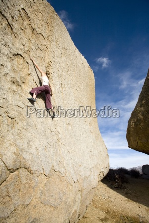 young woman bouldering in bishop ca