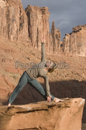 woman in yoga pose on sandstone