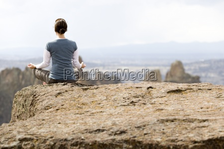a woman meditating on the edge