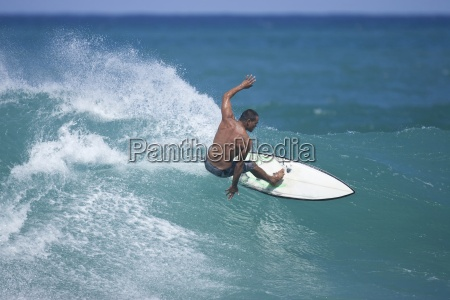 a young man surfing at rocky