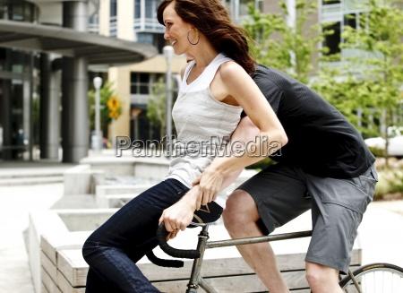 a woman riding on the handlebars