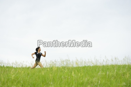 young woman running on grass trail