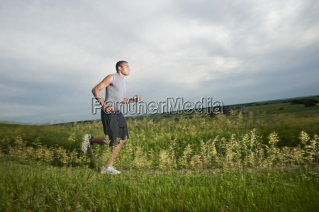 young man running on grass trail