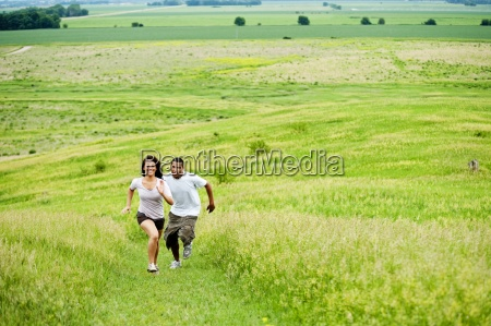 young couple running on grass trail