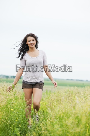 young woman walking carefree through tall
