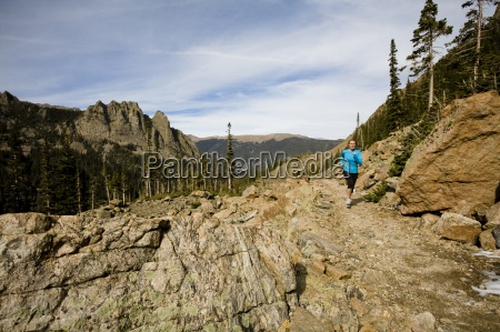 a woman runs along an alpine