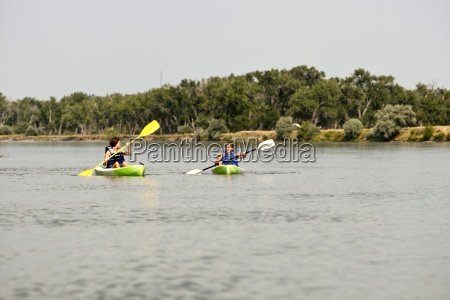 two girls in life jackets paddle