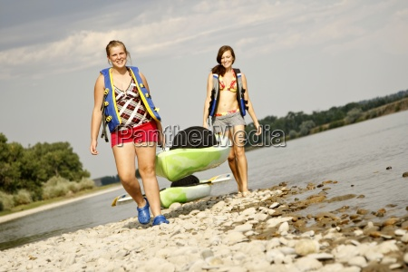 two girls in life jackets smile