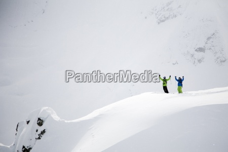 two male skiers raise their hands