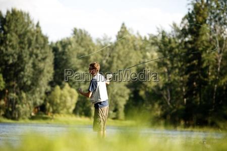 a teenage boy fly fishing in