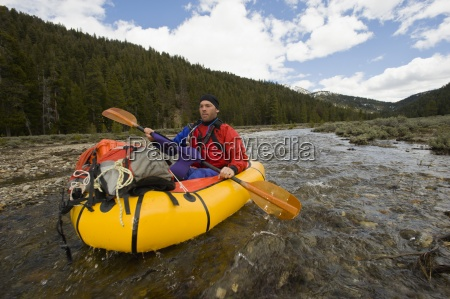 a young man paddles his small