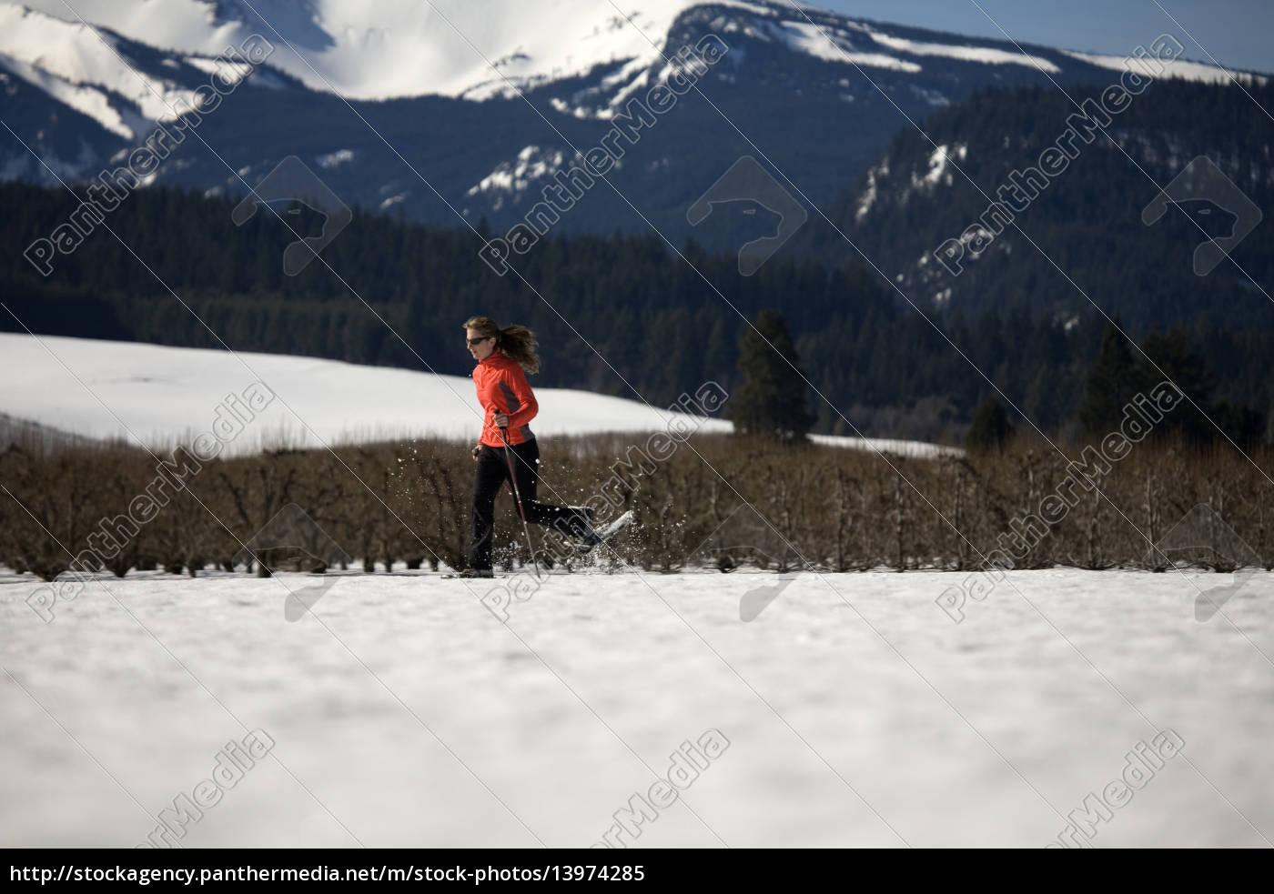 young, woman, runs, through, snow, with - 13974285