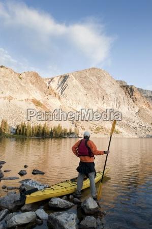a man sea kayaking on lake