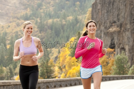 two females smile while jogging in