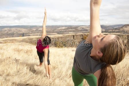two females practicing yoga in the