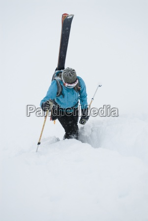 a young woman packs her skis