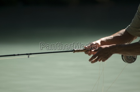 fishermans hands holding a fly fishing