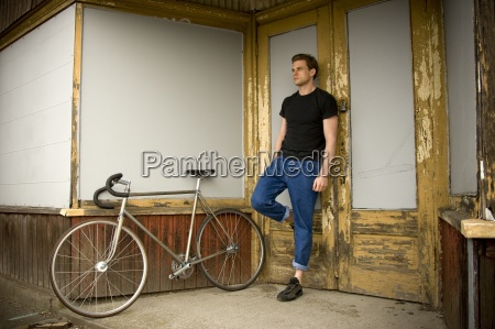 a single speed cyclist leaning against