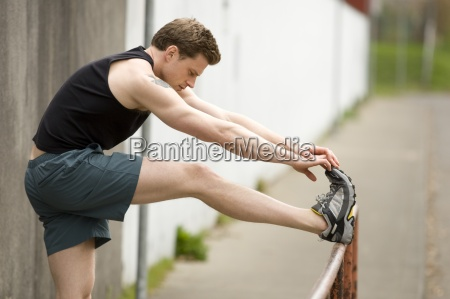 an athletic male stretches before going
