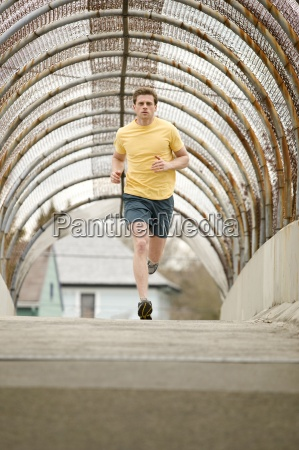 an athletic male jogging through a