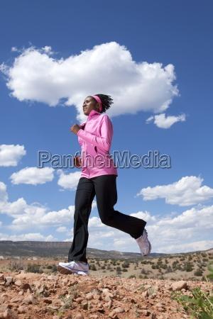 a woman runs along a dirt