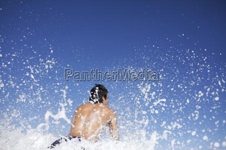 male surfer splashing water at the