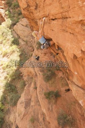 a rock climber ascends a red