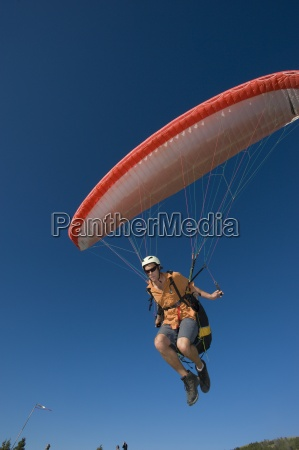 a paraglider lifts off the ground