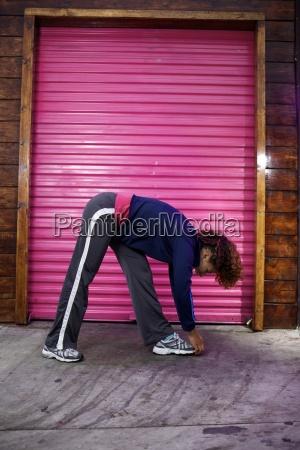 female runner stretches before running in