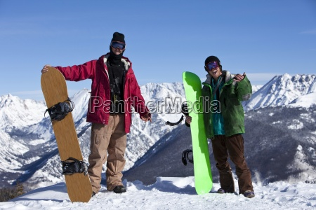 two excited young adult snowboarders in