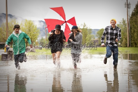 four young adults laugh while running