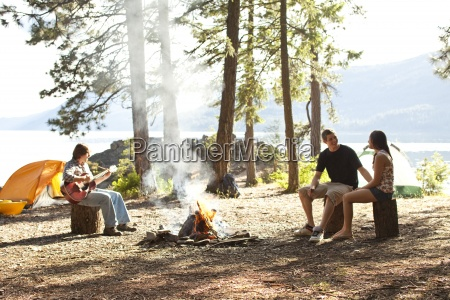 young adults camping sit around a