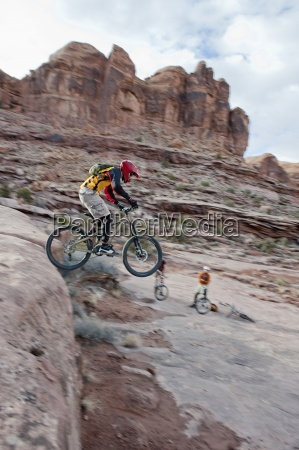 a downhill mountain biker launches off