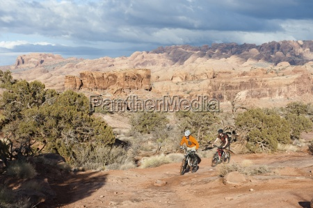 two young men ride their bikes