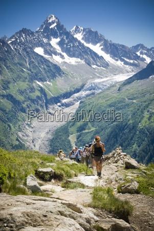 hikers trek up a hill as