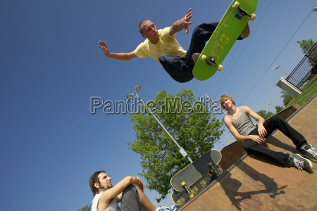 three skateboarders doing tricks at a