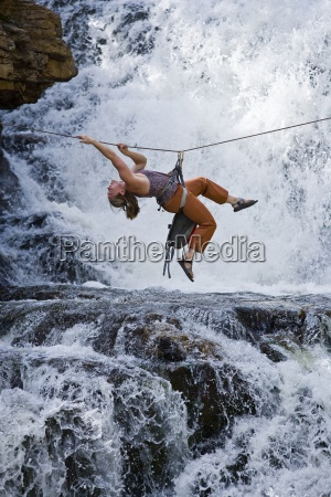 a woman crosses a waterfall using