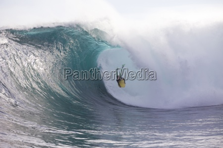 a man bodyboarding a huge wave