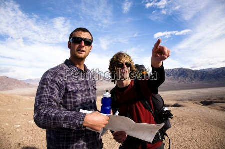 two male hikers look over a