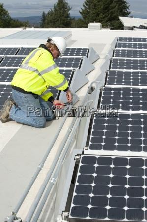 green energy technician adjusts photovoltaic panels