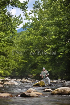 a fly fisherman watches the fly