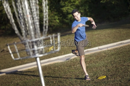 a man playing disc golf attempts