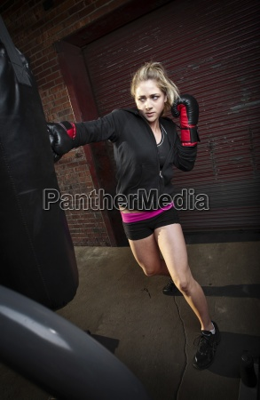a teenage girl punches a punching