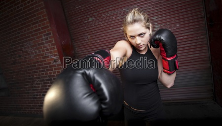 a teenage girl practices punching while