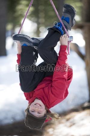 a boy ziplines over the snow