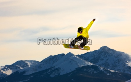 jumping snowboarder flies through the air