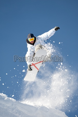 jumping snowboarder with clouds of snow
