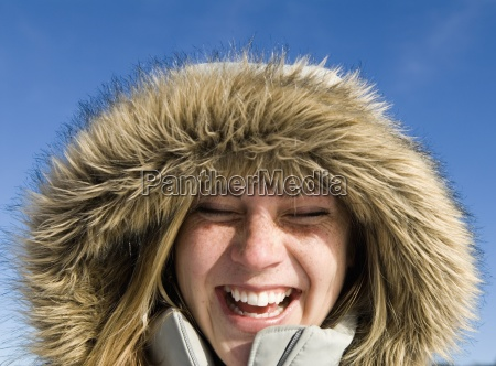 woman outside wearing furry hood